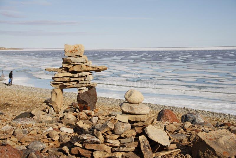 Inukshuk ou Inuksuk sur une plage rocheuse avec de la glace sur l'océan fin juin dans le haut Arctique photo stock