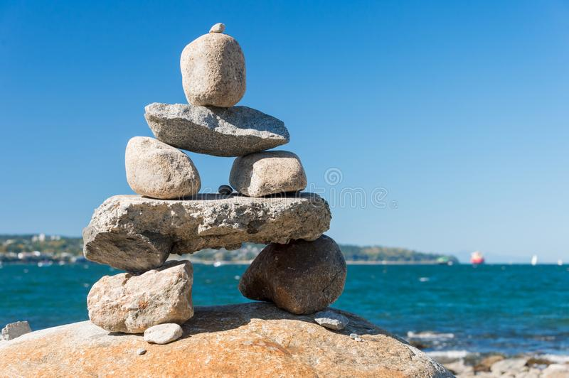 Inukshuk Rock balancing. In Vancouver stone stacking garden English Bay Beach royalty free stock photos