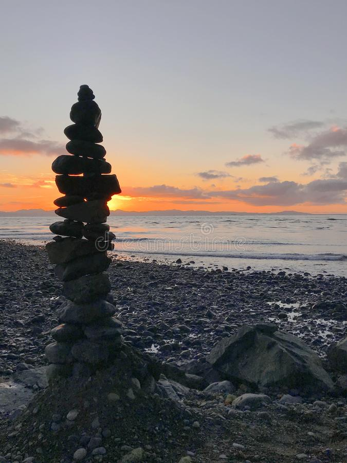 Inukshuk stone statue on the shore at sunset, Jordan River, BC stock images