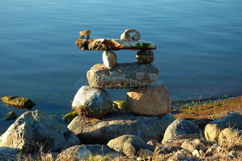 Inukshuk sul bordo dell'acqua fotografia stock