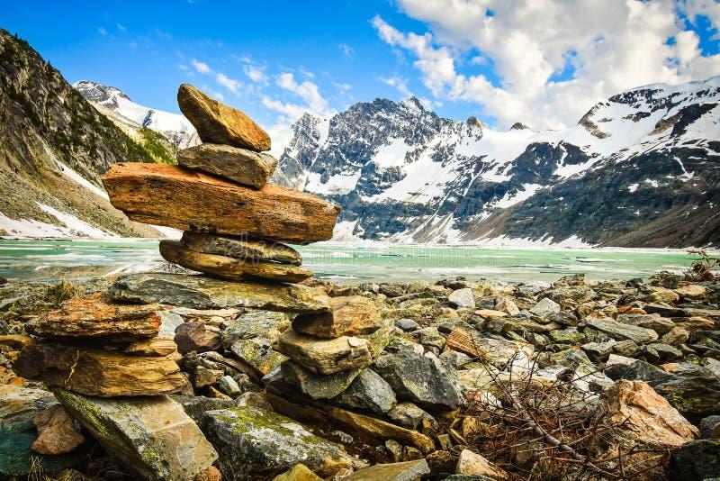 Inukshuk sulla riva, lago ghiacciato, Canada fotografie stock libere da diritti