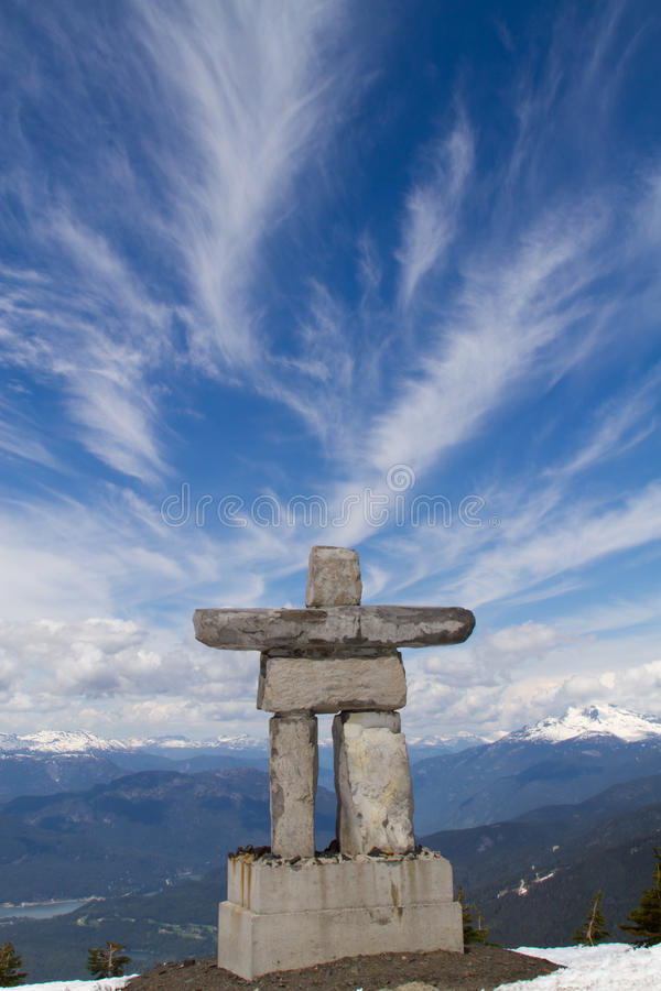 Inukshuk. An Inukshuk on the summit of Whistler mountain in British Columbia with a scenic landscape in the background stock photo