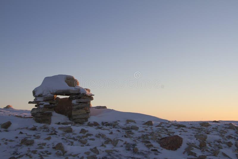 Inuksukoriëntatiepunt in sneeuw bij zonsopgang wordt behandeld op een heuvel dichtbij de gemeenschap van de Baai die van Cambridg royalty-vrije stock afbeelding