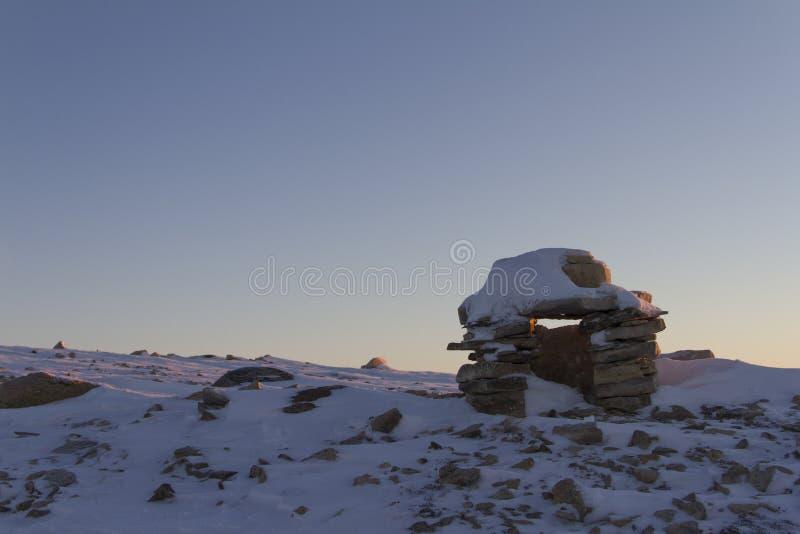 Inuksukoriëntatiepunt in sneeuw wordt behandeld op een heuvel dichtbij de gemeenschap van de Baai die van Cambridge wordt gevonde royalty-vrije stock afbeeldingen