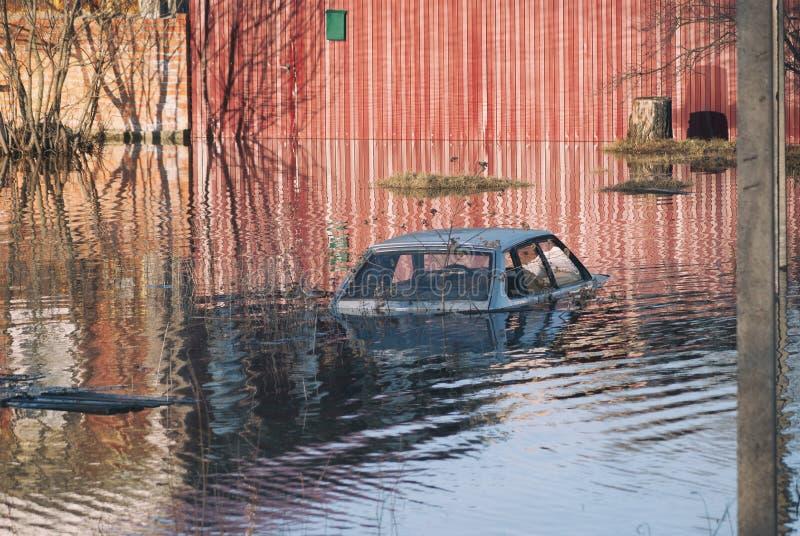 Inundado durante el desastre de la primavera al coche del tejado antes de las puertas de una casa privada Apogeo en la inundación imágenes de archivo libres de regalías