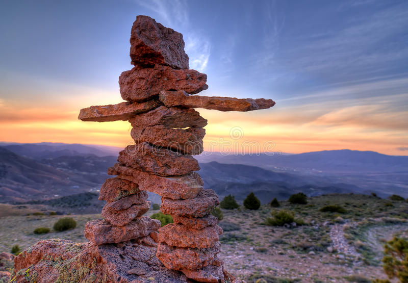 Inunnguaq. Inukshuk rock pile marker in the shape of a human figure against sunrise stock photography
