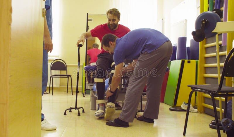 Inválido en la ortosis lista para caminar con la ayuda del bastón que camina dos foto de archivo