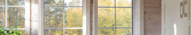Invändigt, rum i trähus med stort fönster banderoll Skandinaviskt format arkivfoto