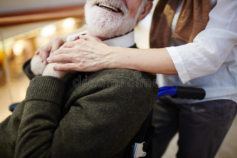 Invalid and caregiver. Smiling aged men in wheelchair and his caregiver stock photo