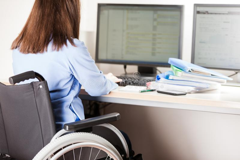Invalid or disabled woman sitting wheelchair working office desk computer royalty free stock images