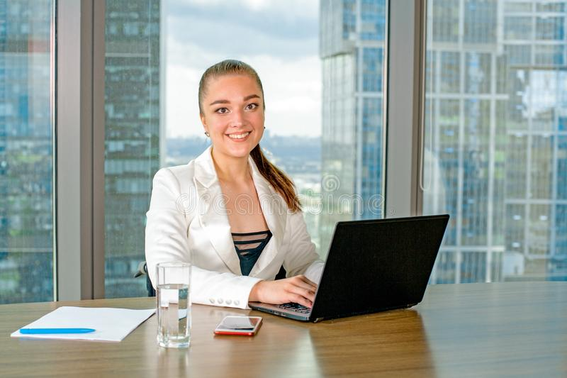 Invalid or disabled young business woman person sitting wheelchair working in office on a laptop royalty free stock images