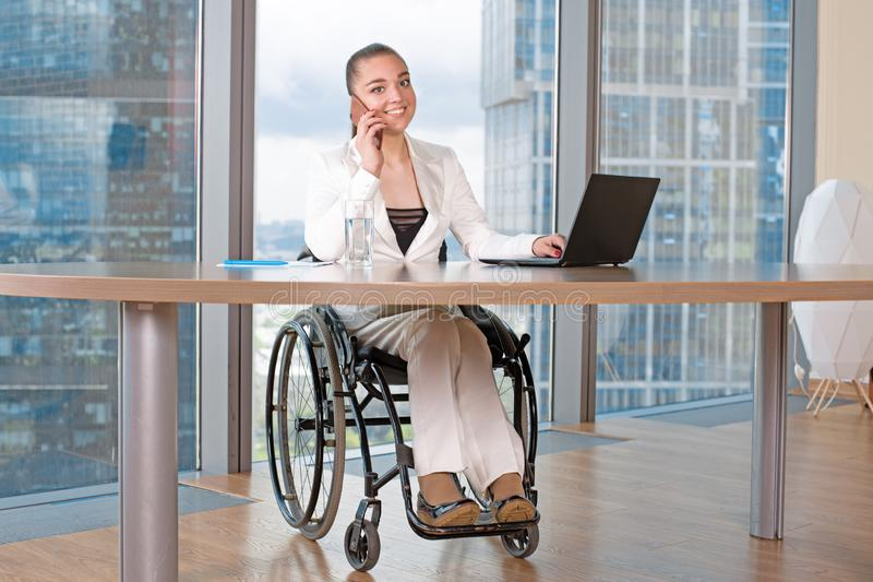 Invalid or disabled young business woman person sitting wheelchair working in office on a laptop. Invalid or disabled young business woman person sitting stock photography