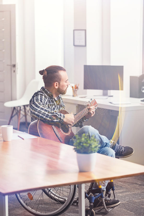 Invalid musician sitting between two tables stock photos