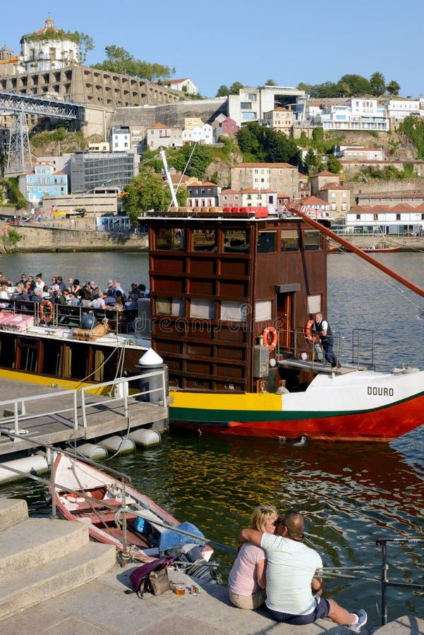 Invallning av den Douro floden som vilar turister Ett par av vänner kysser på flodbanken Romantisk resa arkivbild