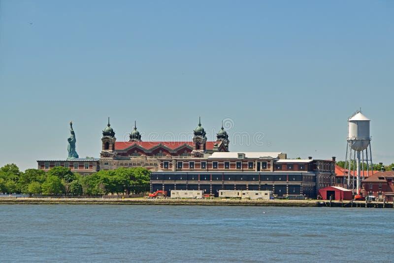 Invandringmuseum på Ellis Island med statyn av Liberty Behind arkivbilder