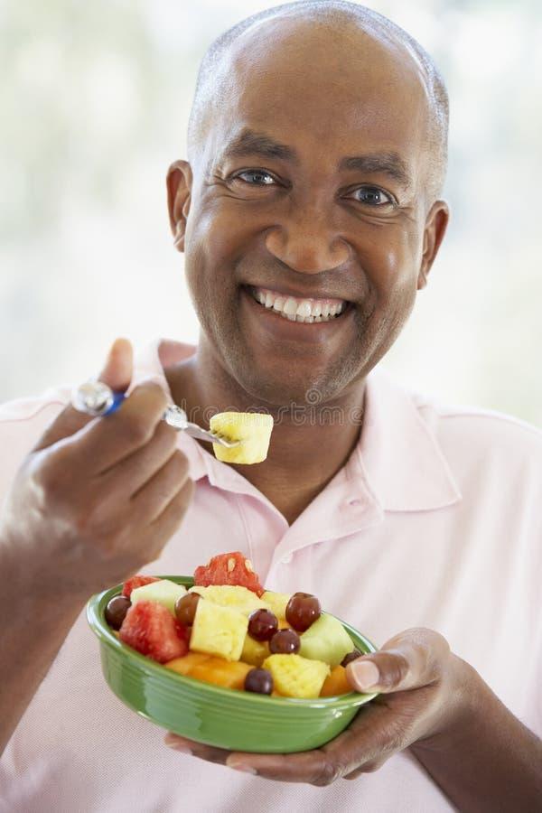 invecchiato mangiando l'insalata della metà dell'uomo della frutta fresca immagine stock