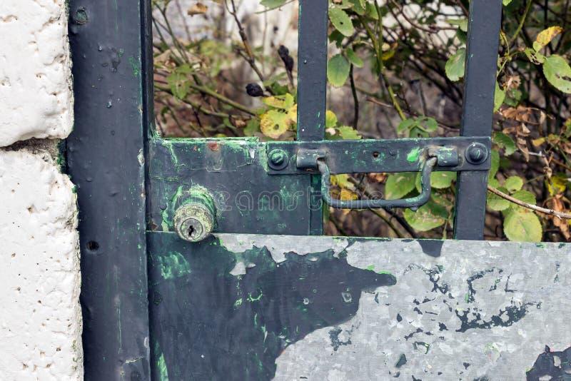 Inverdisca la serratura dipinta del portone di giardino con i punti della ruggine immagine stock