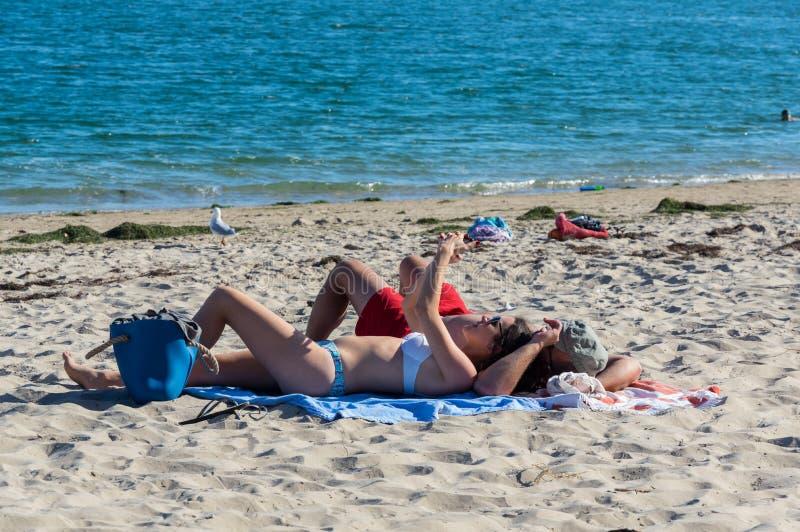 Beachgoers on Inverloch beach in South Gippsland in Australia. Inverloch, Australia - January 27, 2018: young couple lying on Inverloch beach, a popular seaside royalty free stock photography