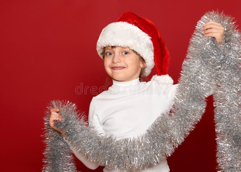Inverno, bambino, concetto di natale - ragazza felice in cappello di Santa con la decorazione su rosso fotografie stock libere da diritti