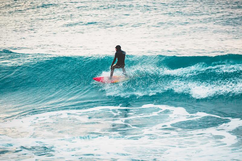 Inverno che pratica il surfing nell'oceano Surfista sull'onda blu immagini stock