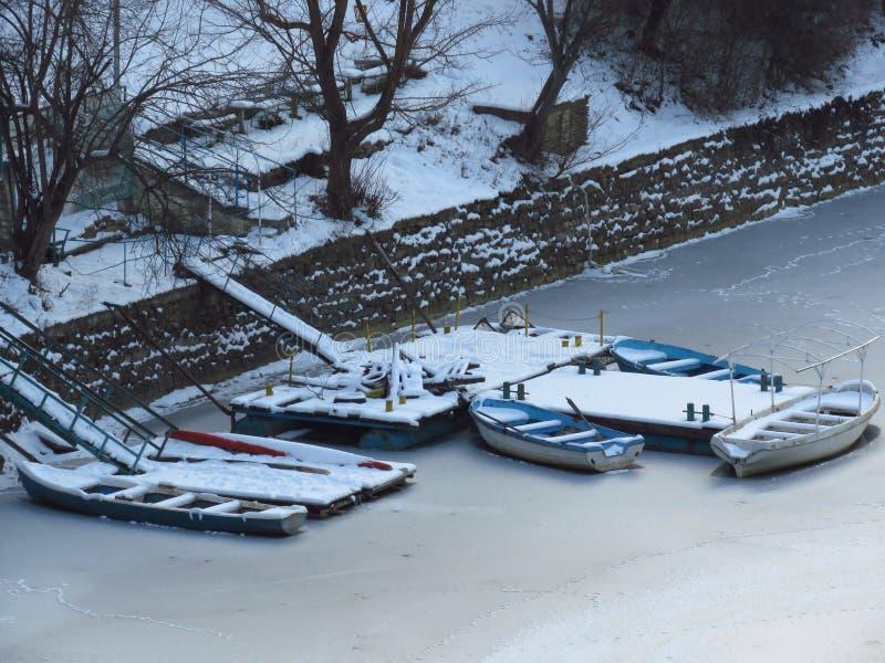 Inverno di congelamento severo Barche congelate in acqua vicino dal fiume congelato costa, stagno, lago, mare immagini stock