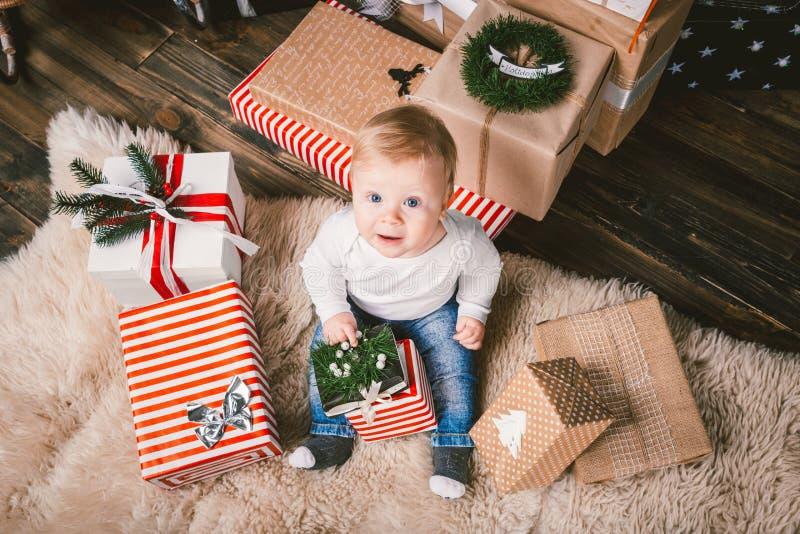 inverno do tema e feriados do Natal Assoalho home de assento do bebê de um ano louro caucasiano do menino da criança perto da árv imagem de stock