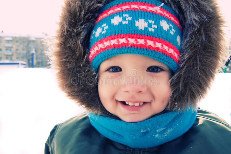 Inverno esterno della neve del ragazzo sveglio. Tempo di natale immagini stock