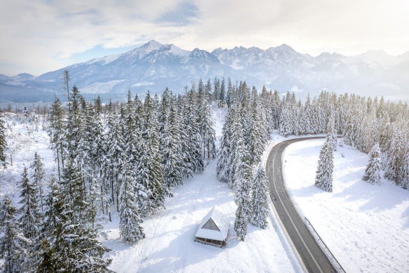 Inverno Montanhas nevados e casa de madeira Fundo do Natal Estrada através dos pinheiros gelados à cordilheira rochosa fotos de stock