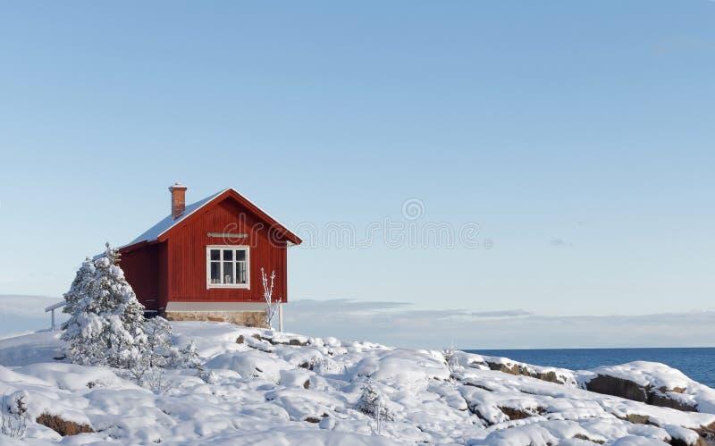 Inverno nel archilelago e nel cottage rosso fotografia stock libera da diritti