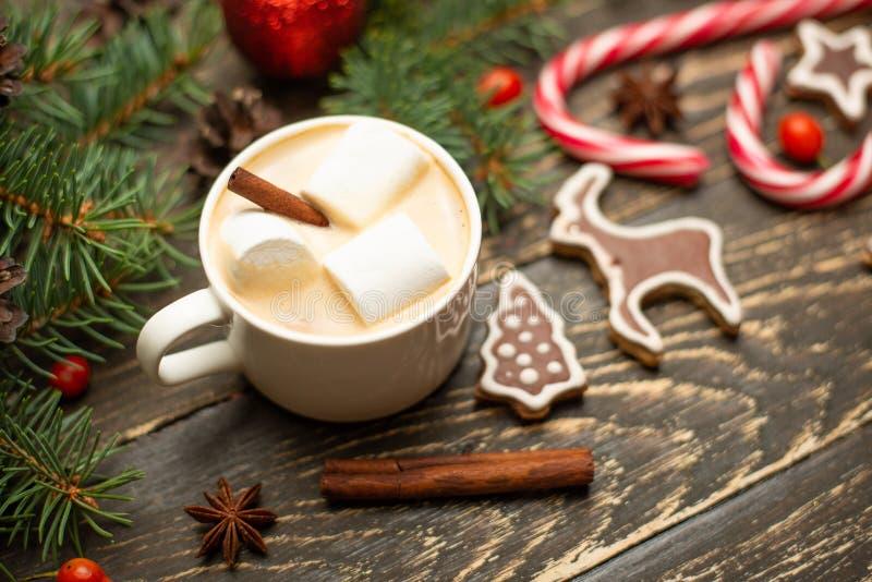inverno que aquece o latte quente da bebida doce com marshmallows e cacau em uma caneca com um bastão de doces do feriado do Nata fotografia de stock royalty free