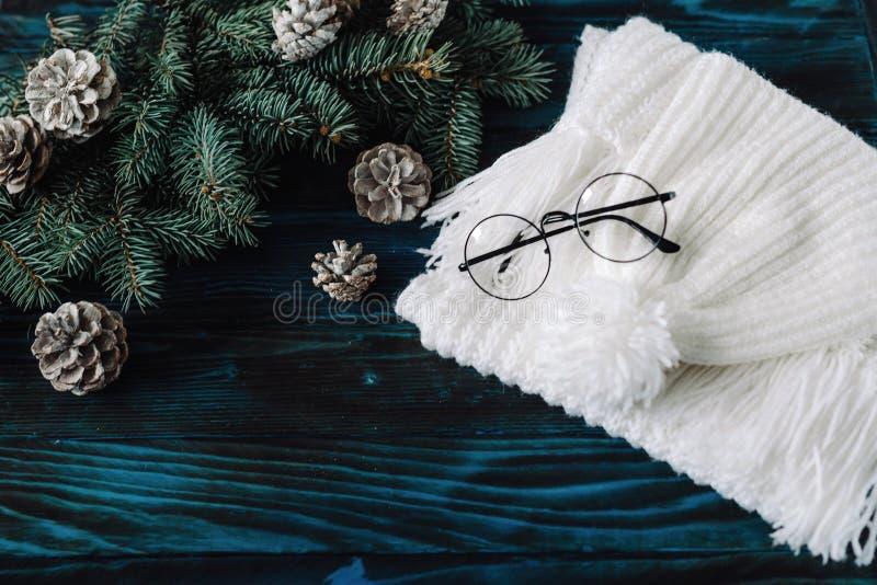 inverno que faz malha bely o lenço e o chapéu, vidros pretos, em uma tabela de madeira azul velha, para a decoração, pinho para u imagens de stock royalty free