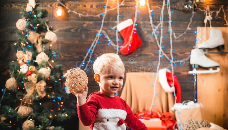 inverno que nivela em casa Presentes da abertura no Natal e no ano novo A criança pequena feliz vestida na roupa do inverno pensa imagem de stock royalty free