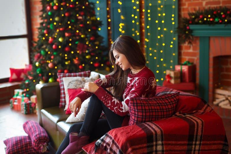 inverno, retrato do xmas: Jovem mulher vestida no casaco de lã de lã morno vermelho que levanta a árvore de Natal próxima interna foto de stock royalty free