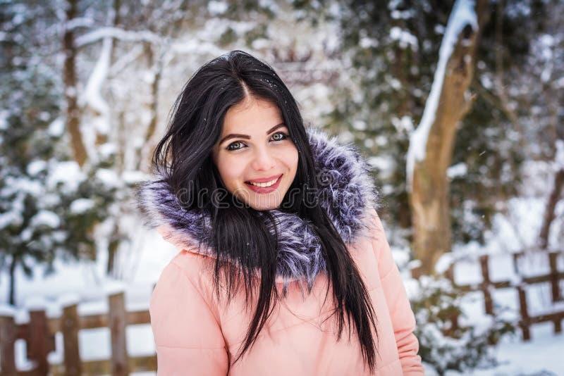 Inverno Sorrisos capless morenos da menina no fundo da neve imagens de stock royalty free