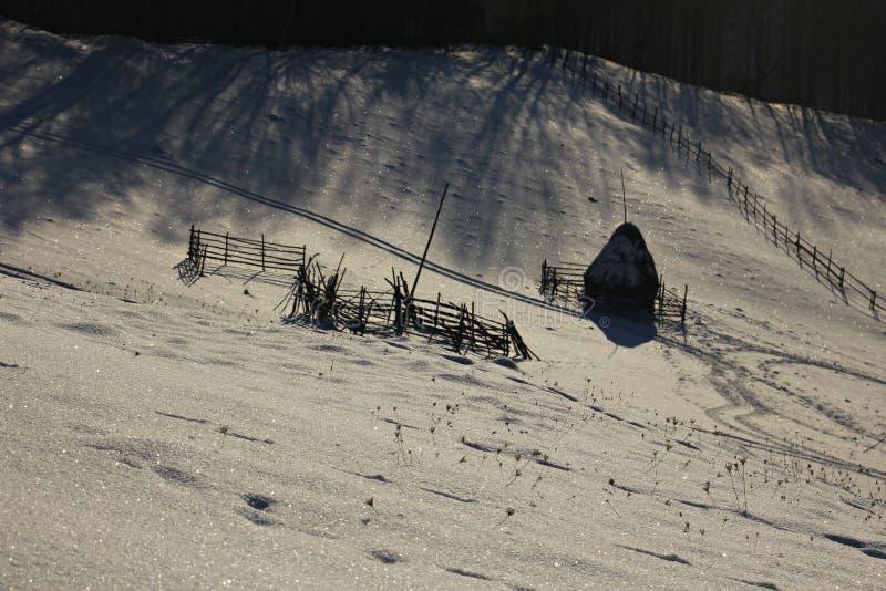 Inverno sulle colline Mucchio di fieno e recinti Ombre nella sera fotografie stock