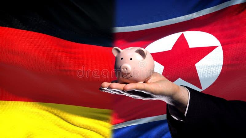Inversión de Alemania en Corea del Norte, mano que lleva a cabo el piggybank en fondo de la bandera imagen de archivo