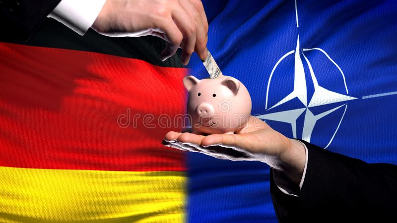 Inversión de Alemania en OTAN, mano que pone el dinero en piggybank en fondo de la bandera foto de archivo libre de regalías