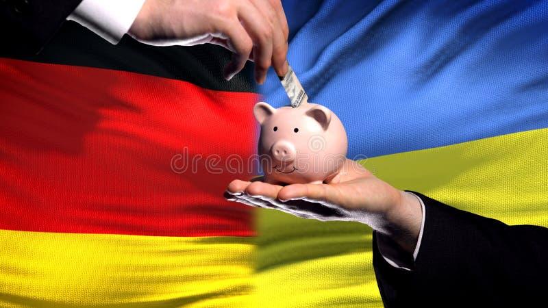 Inversión de Alemania en Ucrania, mano que lleva a cabo el piggybank en fondo de la bandera fotos de archivo