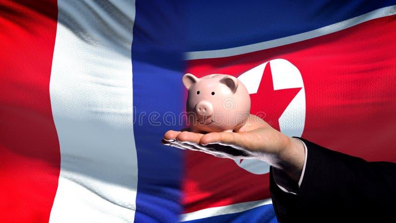 Inversión de Francia en la mano de Corea del Norte que lleva a cabo el piggybank en fondo de la bandera imagen de archivo libre de regalías