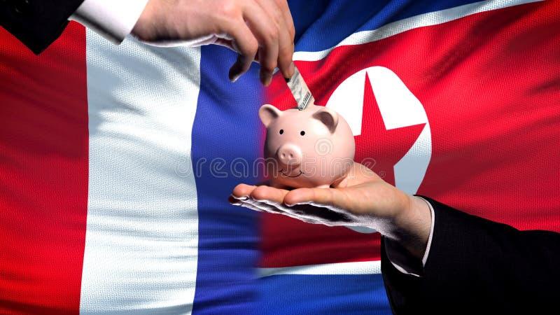 Inversión de Francia en la mano de Corea del Norte que pone el dinero en fondo de la bandera del piggybank imágenes de archivo libres de regalías