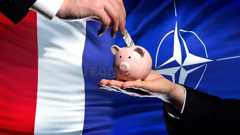 Inversión de Francia en OTAN, mano que pone el dinero en piggybank en fondo de la bandera fotos de archivo libres de regalías