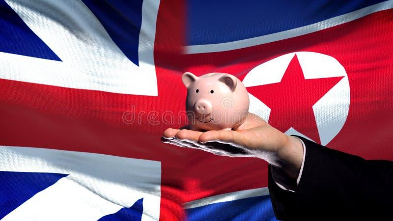 Inversión de Gran Bretaña en Corea del Norte, mano que lleva a cabo el piggybank, fondo de la bandera fotografía de archivo