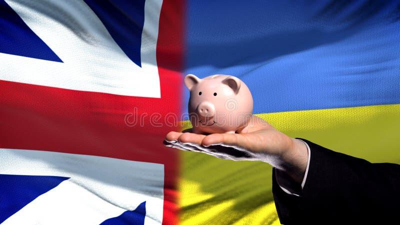 Inversión de Gran Bretaña en Ucrania, mano que lleva a cabo el piggybank en fondo de la bandera imagen de archivo libre de regalías