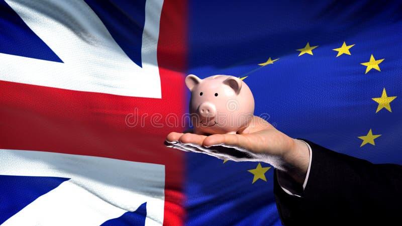 Inversión de Gran Bretaña en UE, mano que lleva a cabo el piggybank en fondo de la bandera imagen de archivo libre de regalías