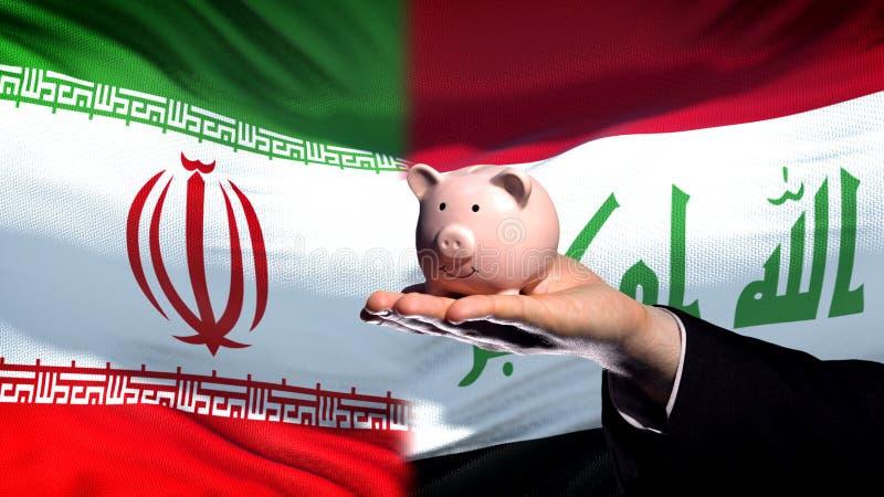 Inversión de Irán en Iraq, mano del hombre de negocios que lleva a cabo el piggybank, fondo de la bandera fotografía de archivo