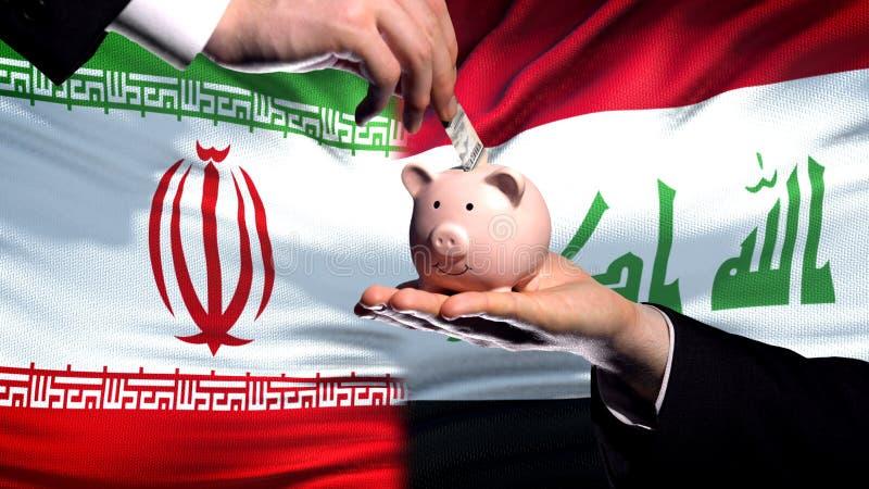 Inversión de Irán en Iraq, mano que pone el dinero en piggybank en fondo de la bandera fotografía de archivo libre de regalías