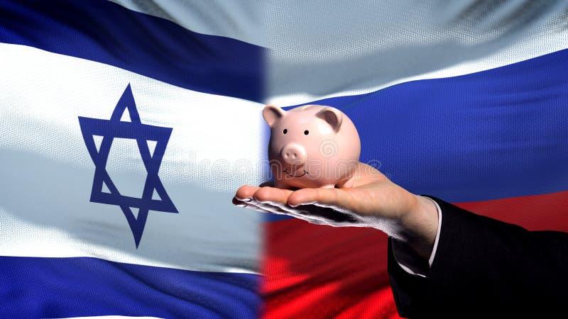 Inversión de Israel en Rusia, mano del hombre de negocios que lleva a cabo el piggybank, fondo de la bandera fotos de archivo libres de regalías