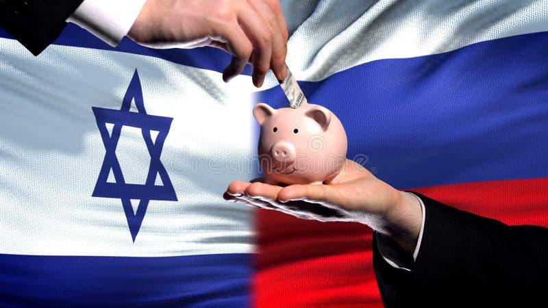 Inversión de Israel en Rusia, mano que pone el dinero en piggybank en fondo de la bandera imagen de archivo