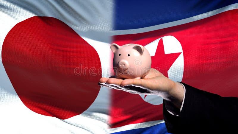 Inversión de Japón en Corea del Norte, mano que lleva a cabo el piggybank en fondo de la bandera fotografía de archivo libre de regalías
