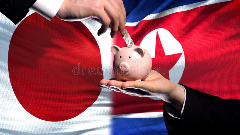 Inversión de Japón en la mano de Corea del Norte que pone el dinero en el piggybank, fondo de la bandera fotografía de archivo libre de regalías